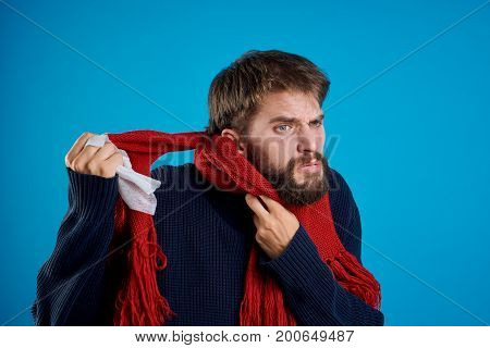 Man with a beard on a blue background ties up a scarf, sweater, flu.