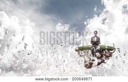 Funny man in red glasses and suit sitting on island and reading book
