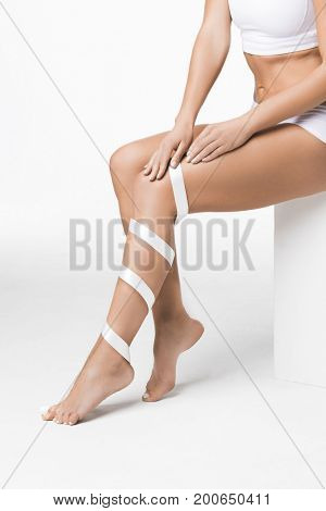 Studio shot of young woman with perfect body with leg wrapped in white ribbon, depilation, varicose concept