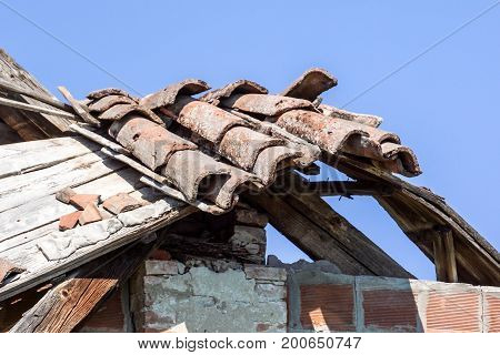 Tile Roof damaged and needing repair . blue sky