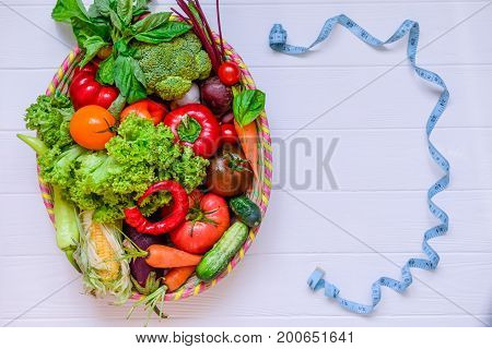 Top View Big Basket With Different Fresh Farm Vegetables And Measuring Tape In Form Of Frame On The