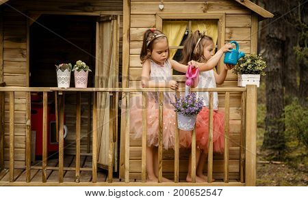 Two lovely girls play with watering can in a tree house in a summer forest