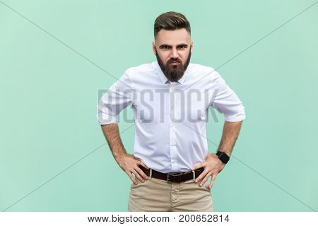 Bad emotions and feelings. Serious man angry look at camera over light green background in studio shot.