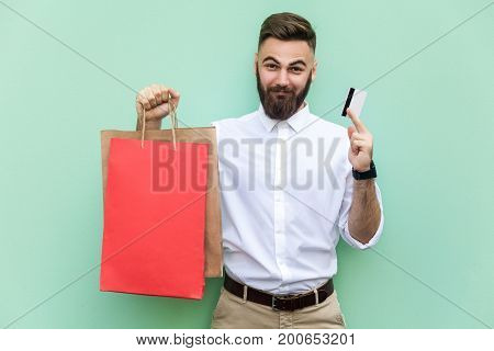 Young adult businessman using credit card for online shopping or banking. Holding credit card on hands and looking at camera and smile. Indoor studio shot. Light green background