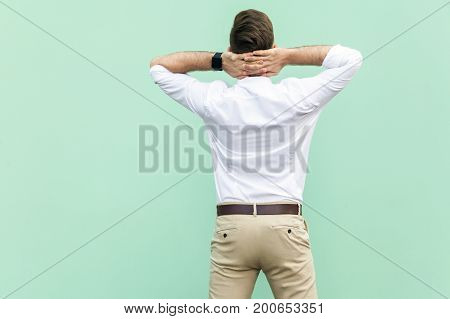 Boss. Succes young adult businessman crossing hand on head and relax. Light green background. Studio shot
