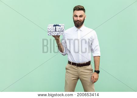 Young adult businessman holding gift box and looking at camera and toothy smile. On light green background. Studio shot