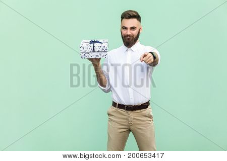 Young adult bearded man pointing at camera and holding a gift box. Studio shot on light green background
