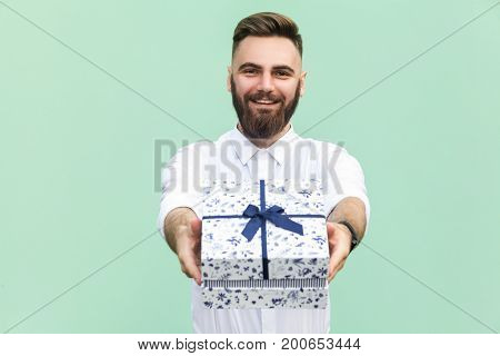 Businessman holding gift box and looking at camera and toothy smile. On light green background. Studio shot