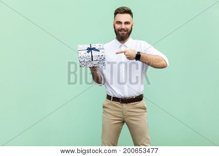 Young adult businessman pointing finger on gift box and looking at camera and toothy smile. On light green background. Studio shot