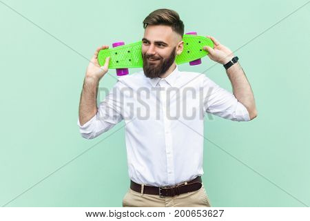 Young adult businessman holding under head his skatelooking left and toothy smiling. Light green background. Studio shot