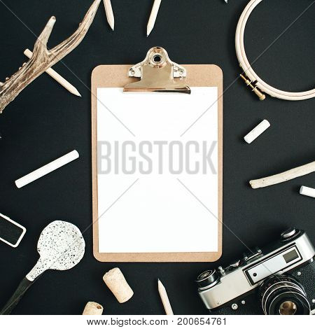 Clipboard mock up with goat horns retro camera handmade spoon pencils and accessories on black chalk board background. Top view flat lay hipster concept.