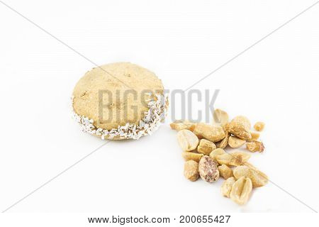 Alfajor of cornstarch with grated coconut and peanuts scattered around. White background.