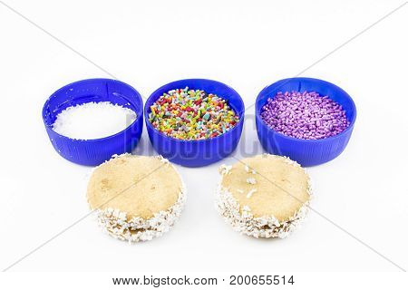 Alfajores of cornstarch made and ingredients for its decoration like dragees and grated coconut. White background.