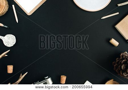 Top view flat lay hipster artist workspace background. Layout with copy space frame decorated with clipboard handmade spoon cone craft diary goat horns retro camera on black chalk board background.