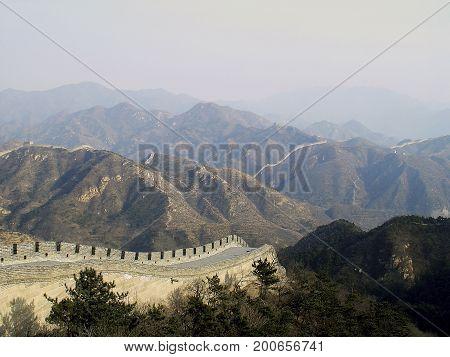 Das Weltwunder Große Chinesische Mauer. Hier sieht man einen kleinen Teil davon wie sich die Mauer kilometerweit über die Berge und Täler hinweg entlang schlängelt. Im Vordergrund ist ein Teil des Walls näher zu sehen.