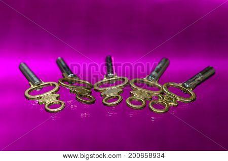 Five Antique Brass Pocket Watch Keys Laying on Purple Surface