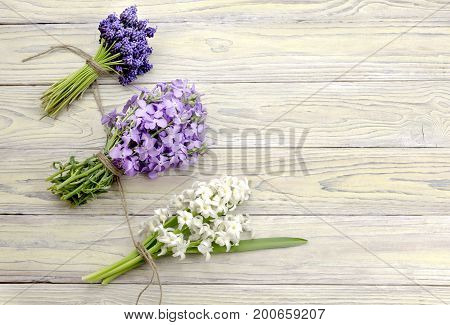 The three bouquets of flowers (hyacinths, muscari and gillyflower) on wooden background close-up