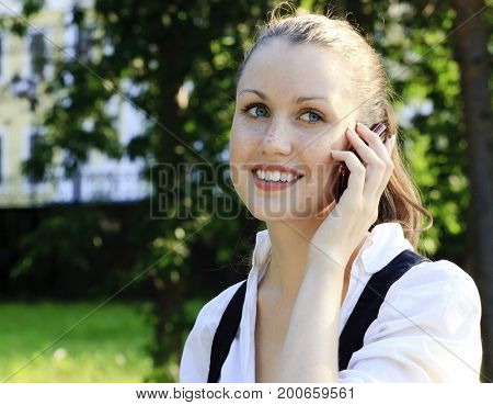 Closeup shot of young smiling woman speaks by a mobile phone