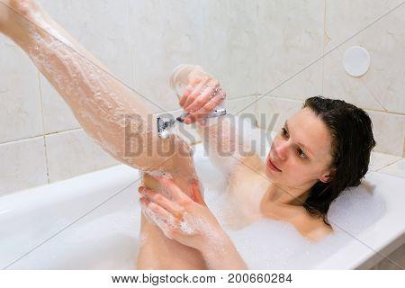 Beautiful young woman enjoying pleasant bath with foam, shaving her leg, focused on legs