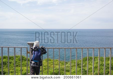 A child stands on the promenade and watching the sea through the fence.