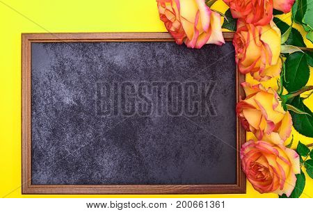 black frame with a bouquet of yellow roses