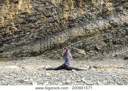 Side view of a healthy mature woman figure stretching and exercising on a rock platform.