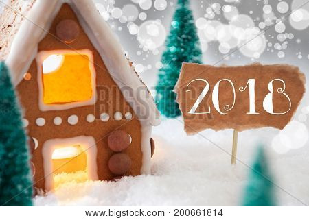 Gingerbread House In Snowy Scenery As Christmas Decoration. Christmas Trees And Candlelight For Romantic Atmosphere. Silver Background With Bokeh Effect. English Text 2018 For Happy New Year
