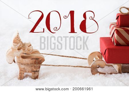 Moose Is Drawing A Sled With Red Gifts Or Presents In Snow. Christmas Card For Seasons Greetings. Text 2018 For Happy New Year Greetings