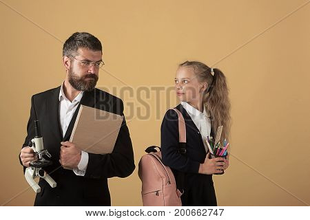 Kid And Tutor Hold Book And Microscope. Girl With Bag