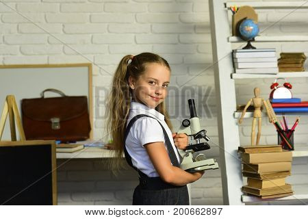 Kid Does Experiments. Girl With Smiling Face Near School Supplies