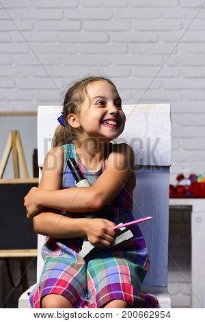 Girl In Her Classroom With Blackboard. Schoolgirl With Happy Smile