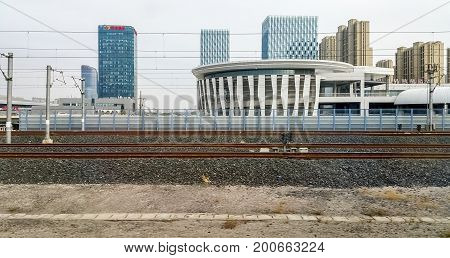 Jinan, China - Nov 1, 2016: High-speed train leaving Jinan Railway Station after a brief stop. Image of modern buildings captured from within the cabin as the train builds up speed.
