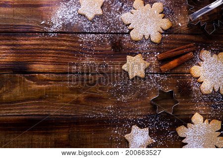 holiday baking background, flour, bakeware, cookie cutter, eggs, cinnamon and cookies on wooden board, view from above with copy space for text