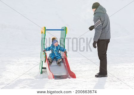 Dad walks with his son in the winter and rolled down the hill.
