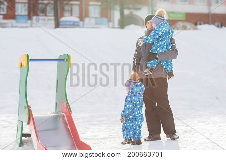 Dad holding twin brother in the hands, the other to take stands on the snow, tconcept of paternity.