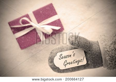 Glove With Label With English Text Seasons Greetings. Pink Or Rose Gift Or Present On Snow In Background. Seasonal Greeting Card With Snowflakes And Instagram Filter
