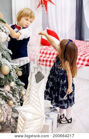 Little brother and sister decorates a Christmas tree in the room. Concept winter lifestyle Merry Christmas.
