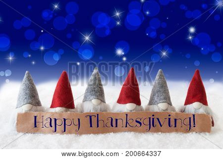 Label With English Text Happy Thanksgiving. Christmas Greeting Card With Gnomes. Sparkling Bokeh And Blue Background With Snow And Stars.