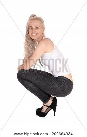 A beautiful smiling young blond woman in a white t-shirt and black jeans crouching in high heels on the floor isolated for white background