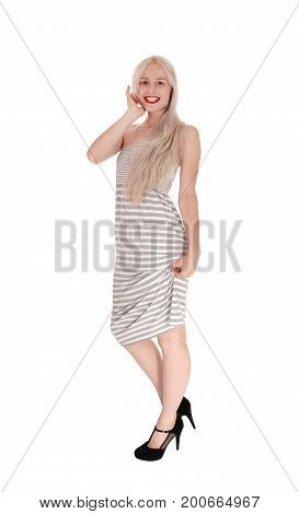 A gorgeous smiling young woman standing in a gray dress and heels smiling with her long blond hair isolated for white background