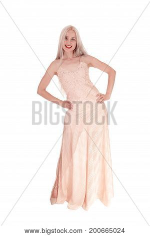 A lovely smiling young woman with long blond hair standing in a long light pink evening dress isolated for white background