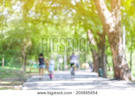 Blurred background of people activities in park with bokeh light spring and summer