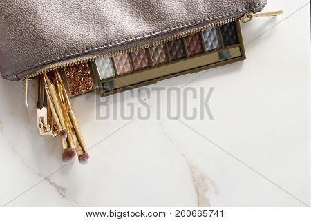 Styled make up bag with eyeshadows, gold brushes, nail clipper, and tweezers. White marble copy space.