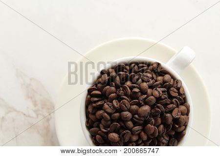 Above view of a white cup and saucer filled with coffee beans against white marble copy space.