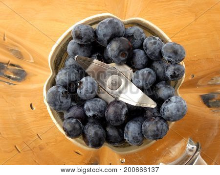 Blueberries in blender juicer on wooden board
