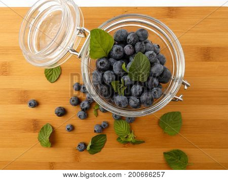 Blueberries in a glass jar on a wooden board