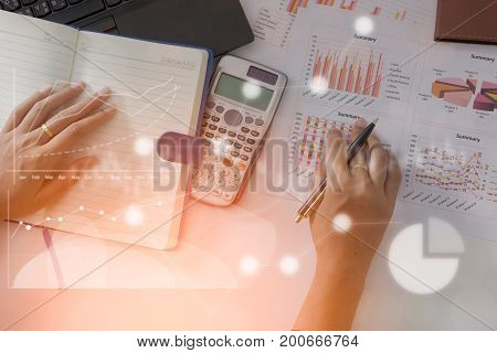 Young finance market analyst working at office on laptop while sitting at white table.Businessman analyze document and the calculator in hands.Graphs and diagram on notebook screen
