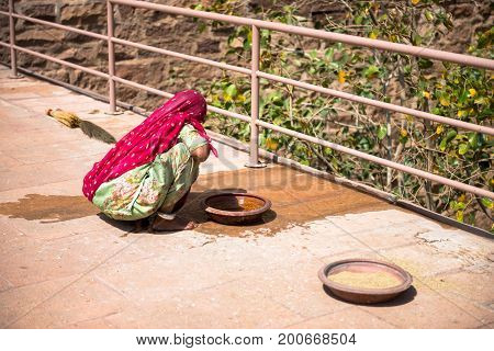 JODHPUR RAJASTHAN INDIA -MARCH 05 2016: Horizontal picture of Indian woman working at Mehrangarh Fort in Jodhpur the blue city of Rajasthan in India.