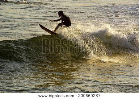 Boy surfing at sunset on Arpoador beach in Ipanema