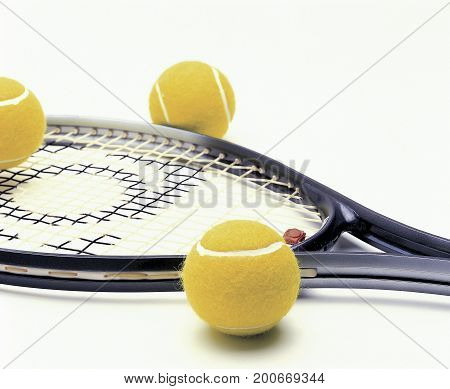 Tenis racquet and some yellow tennis balls